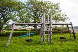 シーソーにタイヤのブランコ。周囲には桜の木があります。
